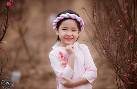 Bé gái 6 tuổi diện áo dài bên vườn đào
